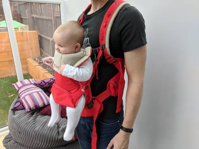 A baby carrier with child in front facing position