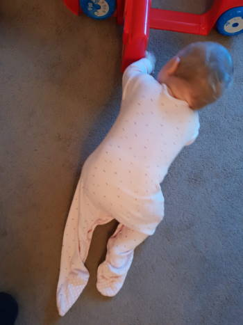 Baby crawling out of a sleep suit