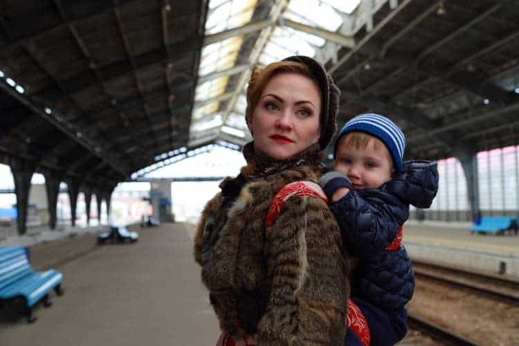 Woman with baby carrier in warm coat at train station