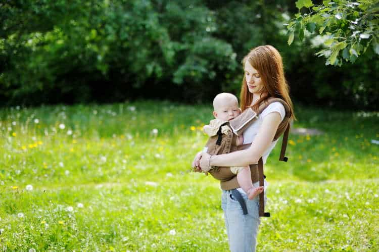 Petite mother with baby in carrier