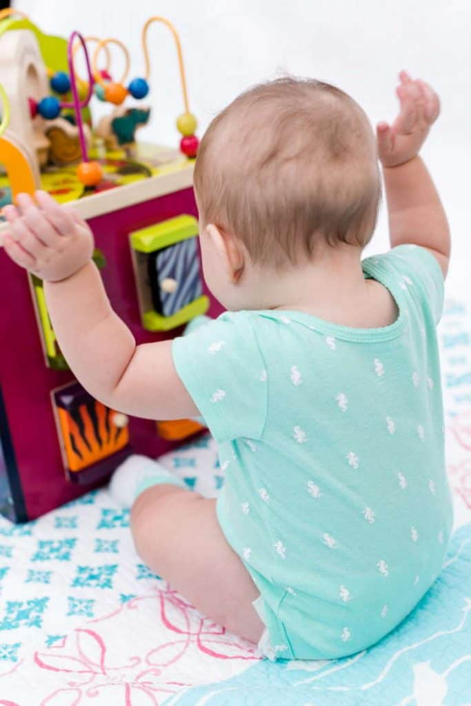 Baby sitting in front of an activity cube