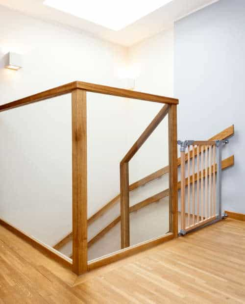 A baby gate at the top of a steep staircase