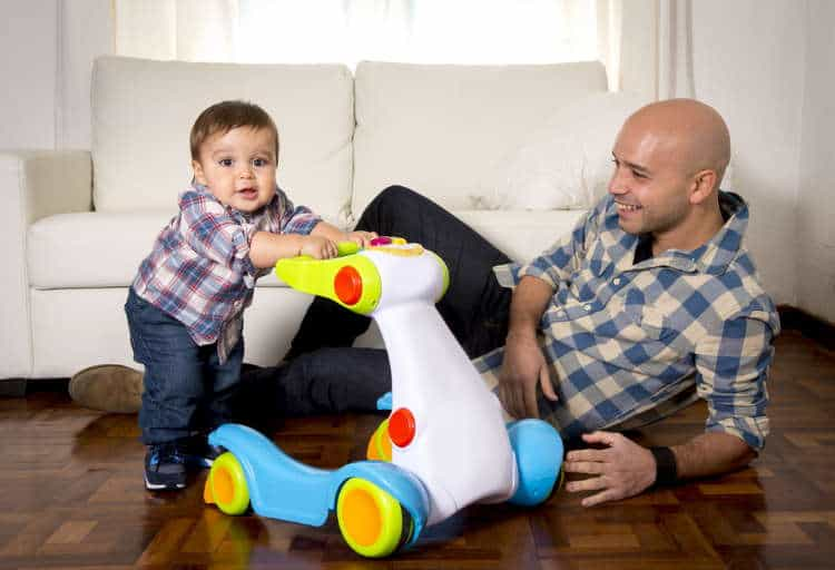 Toddler using a push walker with dad