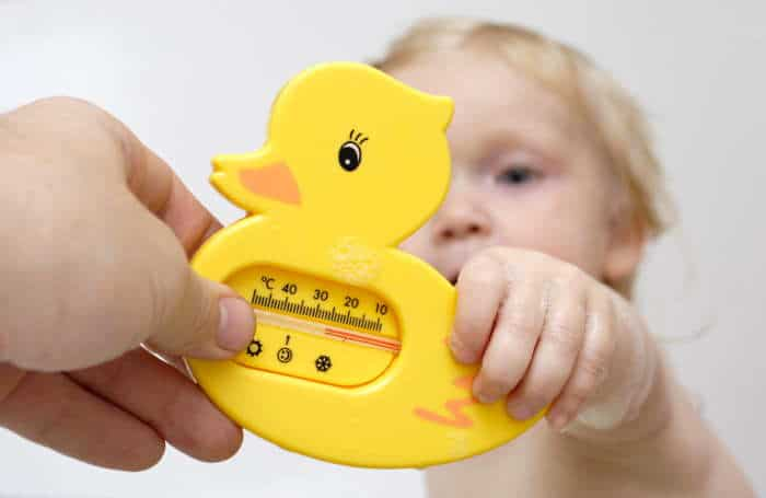 a baby holding a duck bath thermometer