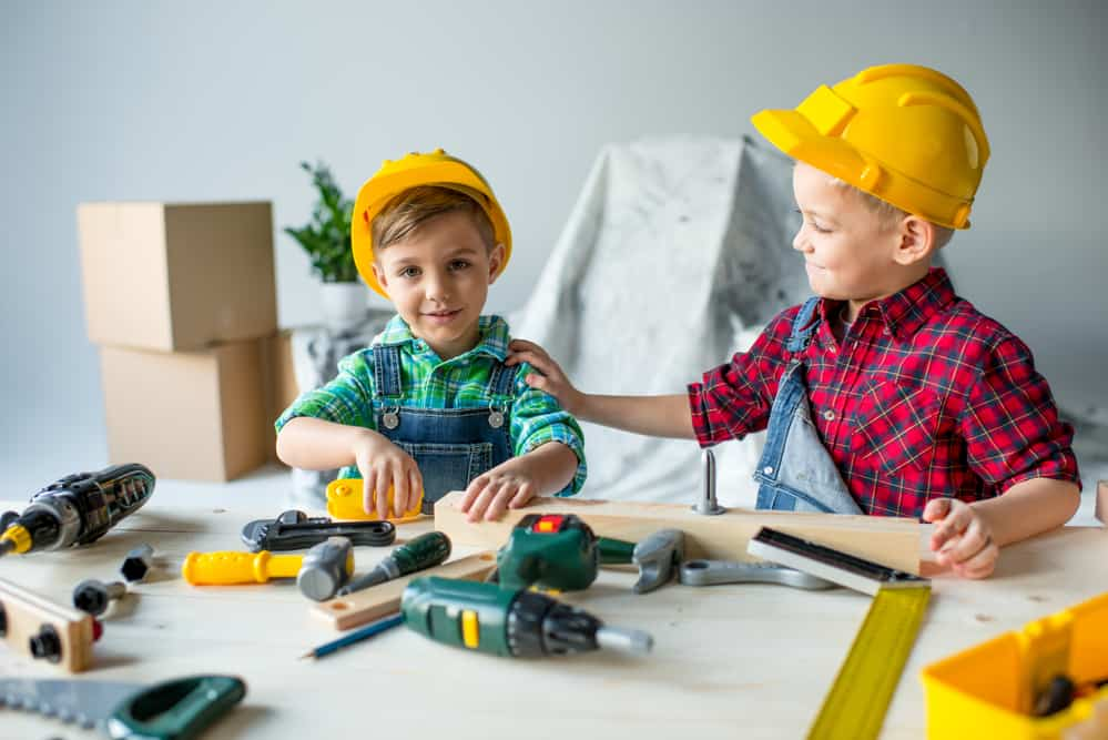 2 kids playing with toy tools on a workbench