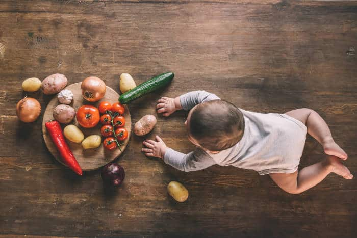 A baby crawling towards a selection of vegetables