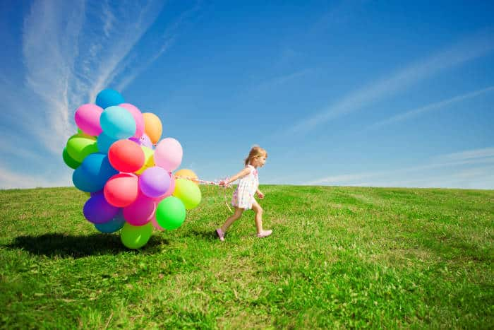 Girl with party ballons in a field