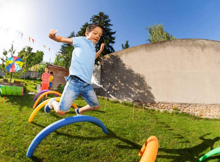 Child jumping over obstacles outside on a sunny day