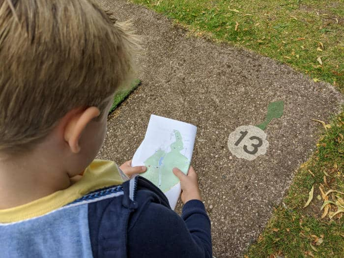 Boy looking at a map and finding a number on the floor