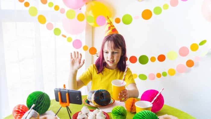 Girl having a virtual birthday party surrounded by decorations and cake