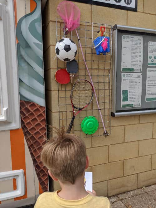 Boy looking at a display of things hanging on a wall