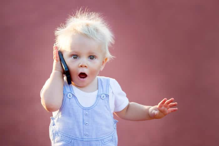 a cute baby with a surprised expression using a cell phone