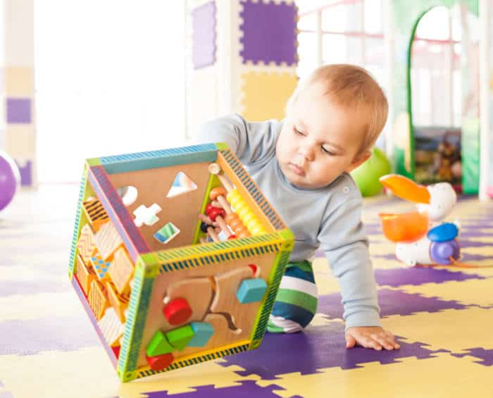 baby boy playing with an activity cube