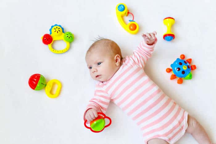 baby surrounded by baby rattles