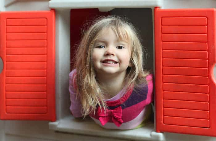 Little girl smiling through the window of kids playhouse