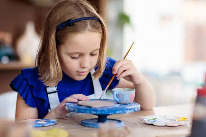 young girl working on a craft or pottery wheel
