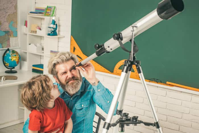 father and son using telescope together
