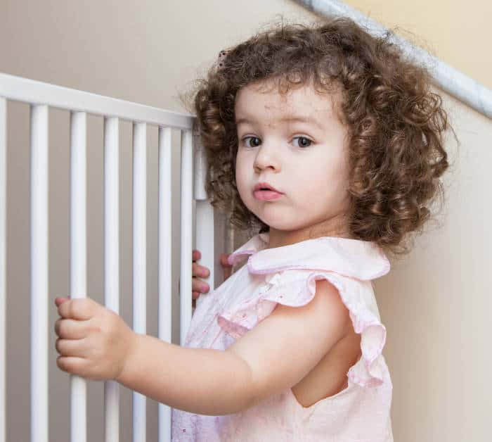 cute toddler girl standing at a baby safety gate