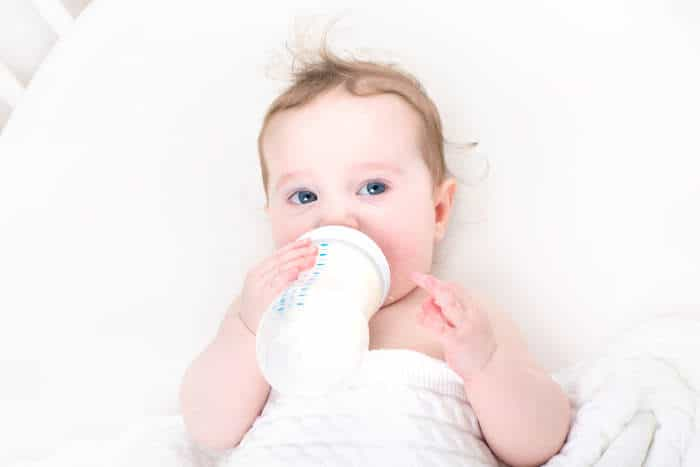 Baby holding own milk bottle and drinking