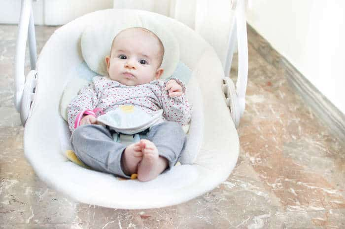 baby in an electronic baby swing seat