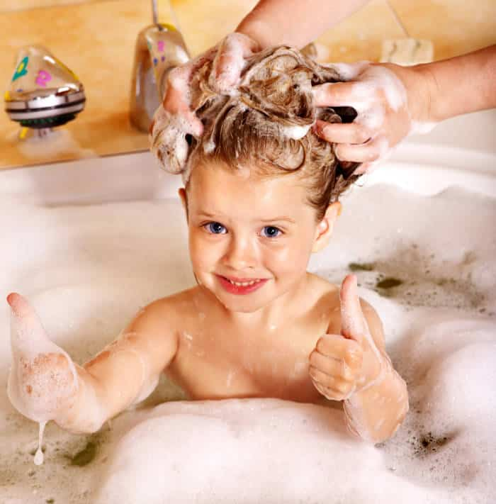 Young girl having hair washed in the bath