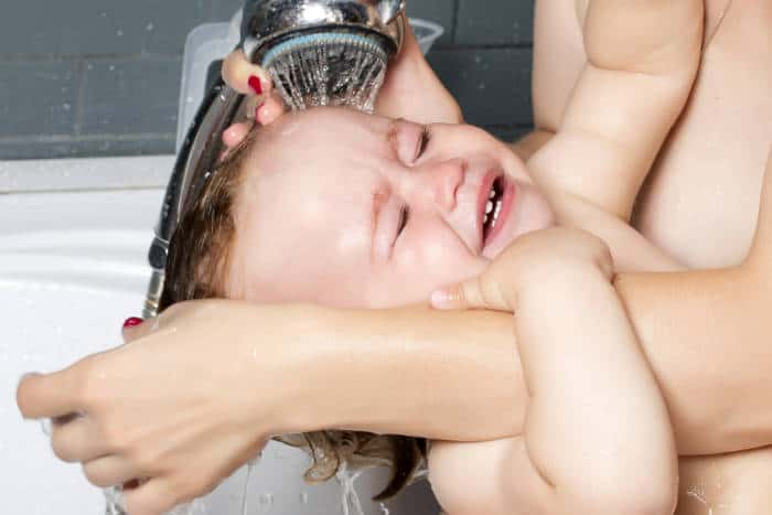 Baby having hair washed under shower head