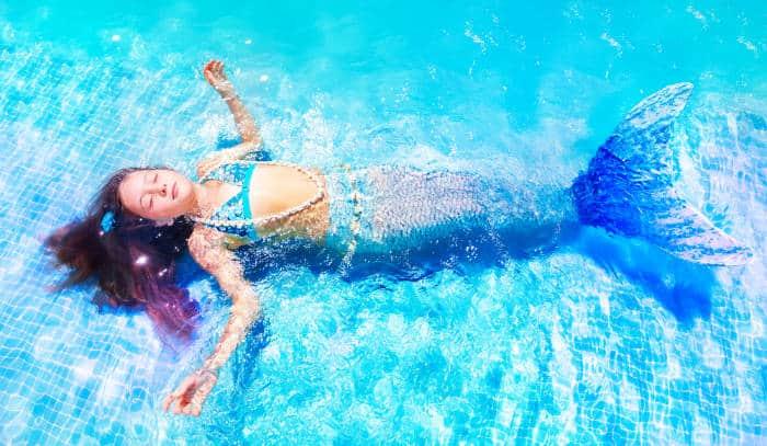 girl dressed as a mermaid floating in the pool
